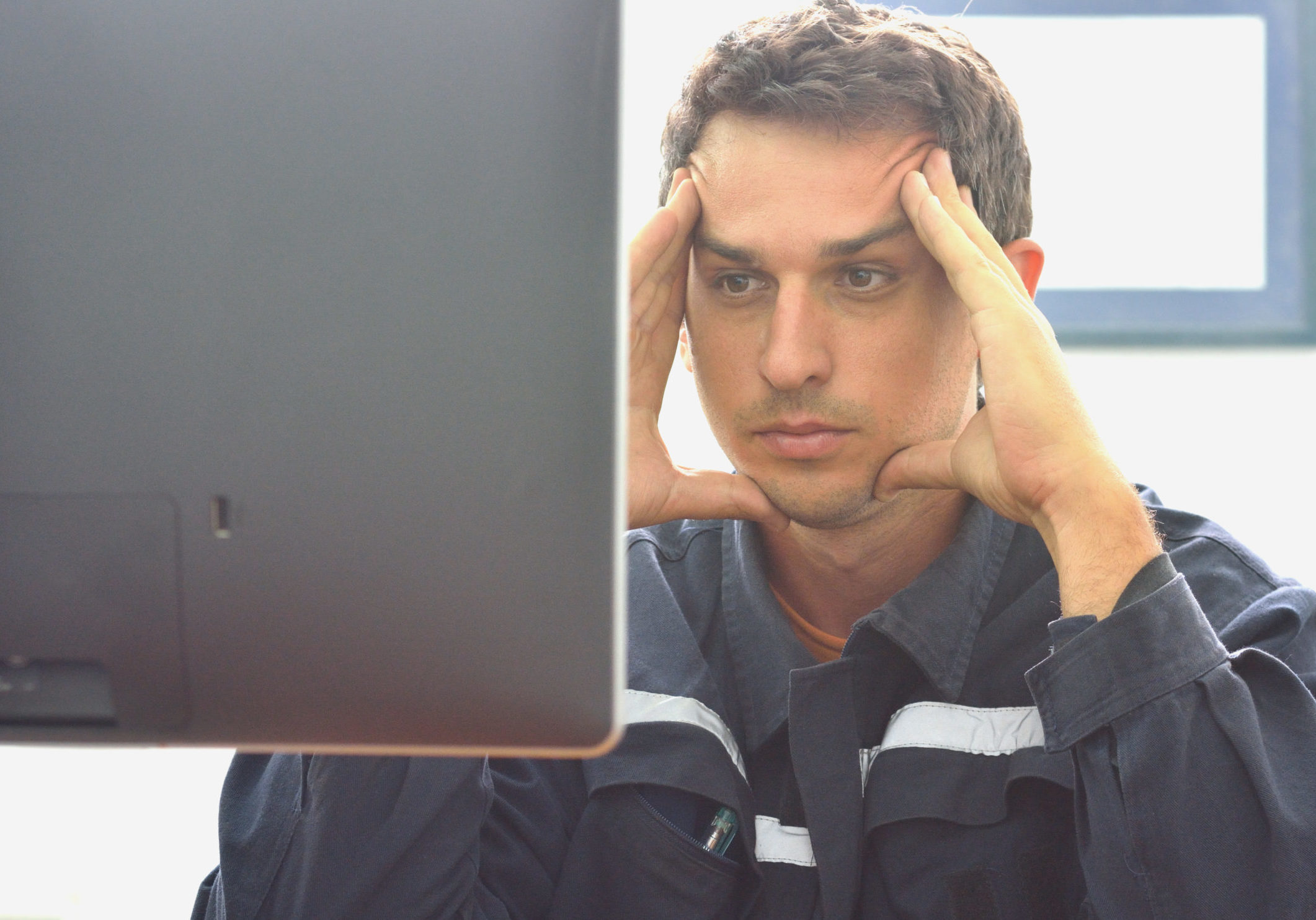 Technician working hard on computer in control room.